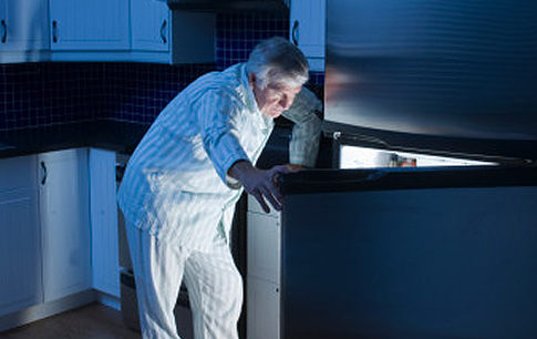 Senior man looking in refrigerator at night Original Filename: 73032480.jpg