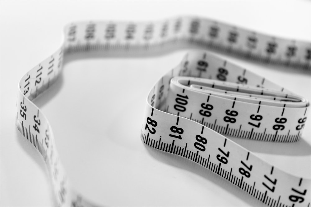 Weight loss concept with measuring tape on a white background.