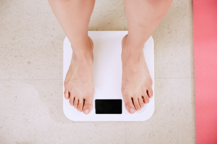 A person checking if they have lost any weight by standing on a weighing scale