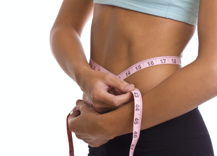 a person measuring their abdomen with a measuring tape