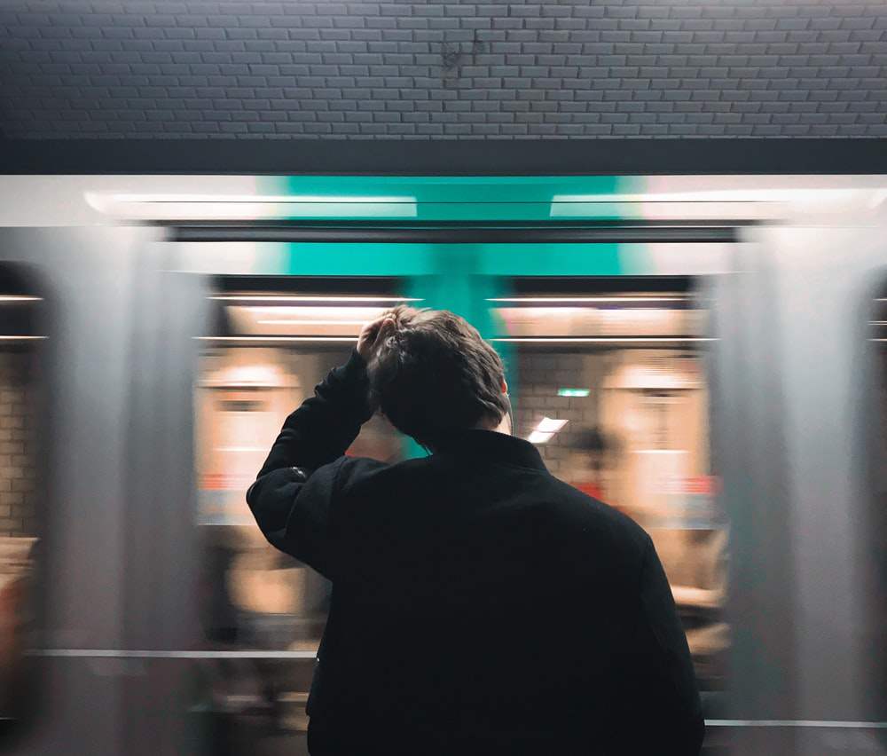 a person stands past a whirring train