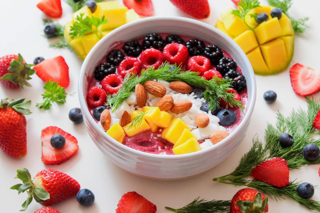 A delicious bowl of yogurt, raspberries, mangoes, and nuts