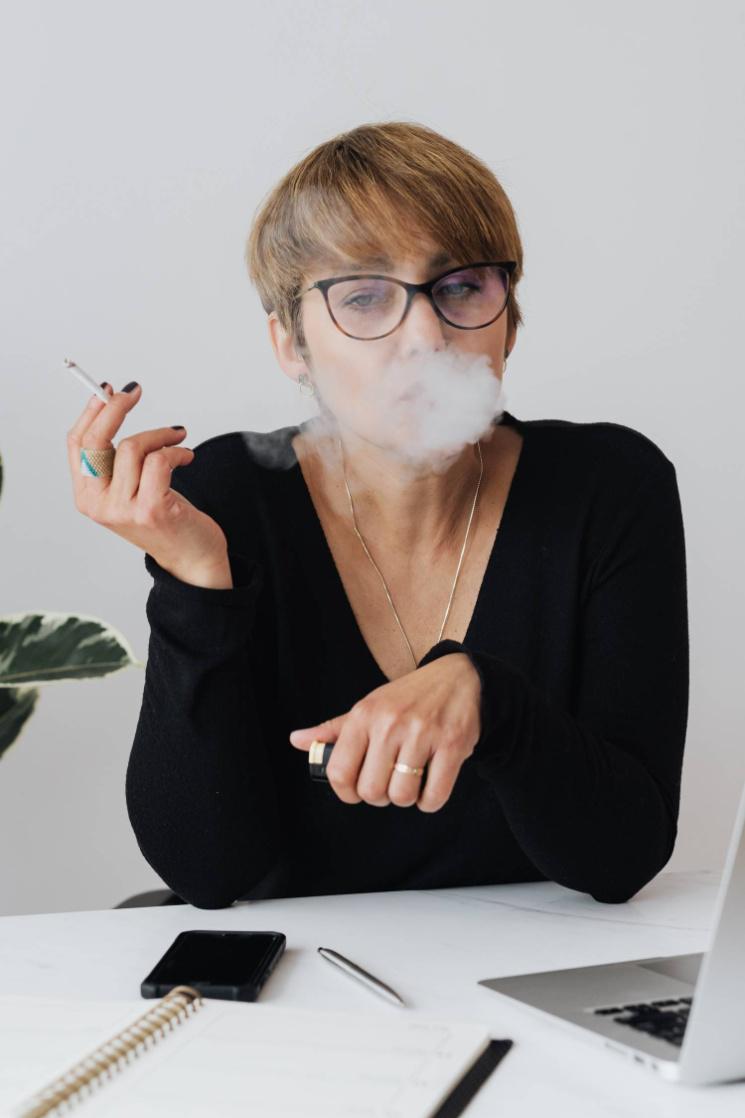 Female employee smoking cigarette