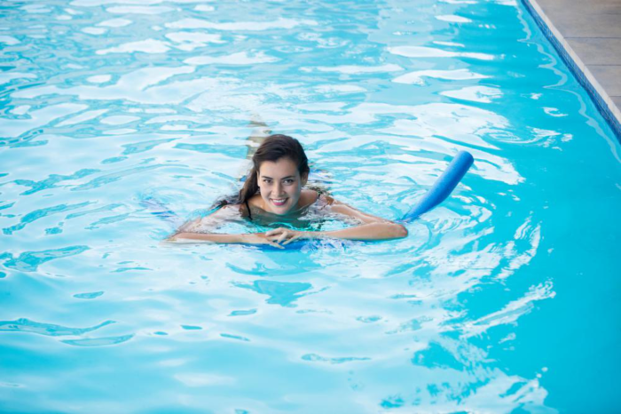 a young woman swimming with an inflatable tube in the pool